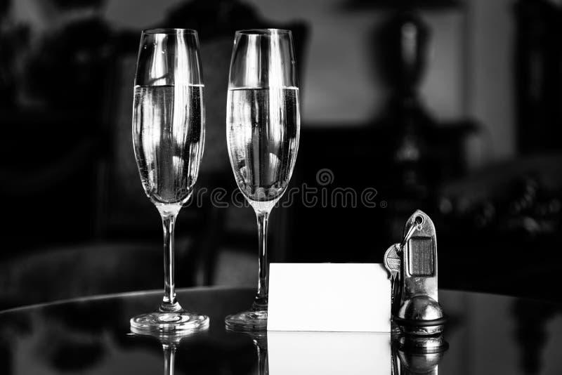 Fulla champagneexponeringsglas, antikvitettangenter och tomt vitt kort Lägenhet för lyxigt hotell arkivfoton