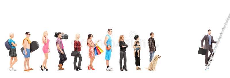 Fulla längdstående av folk som väntar i en linje och en affär royaltyfria foton