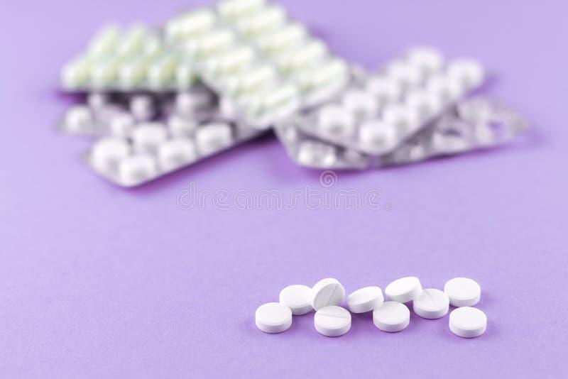 Fulla och tomma packar av vita kapslar och preventivpillerar packade i blåsor med kopieringsutrymme på purpurfärgad bakgrund Foku royaltyfria foton
