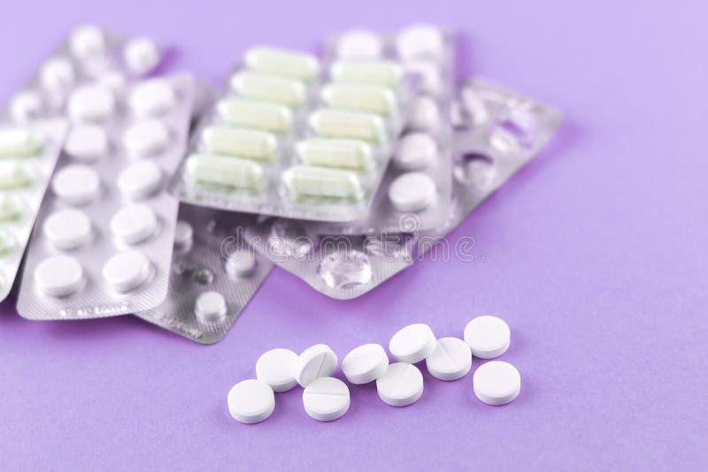 Fulla och tomma packar av vita kapslar och preventivpillerar packade i blåsor med kopieringsutrymme på purpurfärgad bakgrund Foku arkivbild