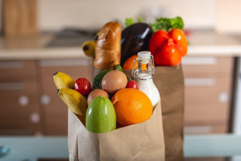 Fulla pappers- påsar med foods på tabellen på bakgrunden av köket Sunda ecoprodukter för en allsidig kost arkivfoton