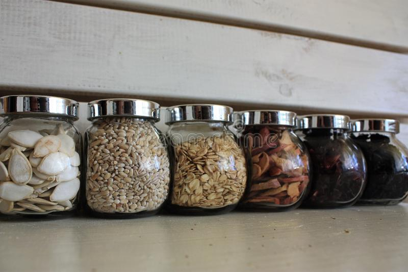 Fulled avec le thé, les graines et les banques en verre sèches de fruits sur le fond blanc en bois image libre de droits
