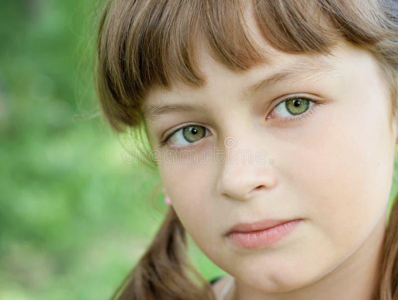 Fullface portrait of serious little girl stock photography