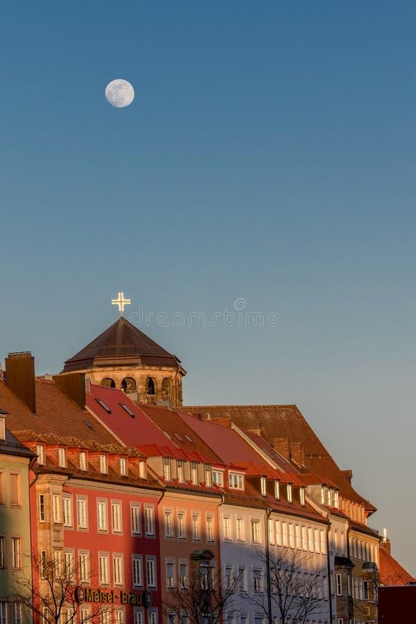 Fullmåne över Bayreuth (Tyskland - Bayern), ortogonalt kyrkligt torn arkivfoto