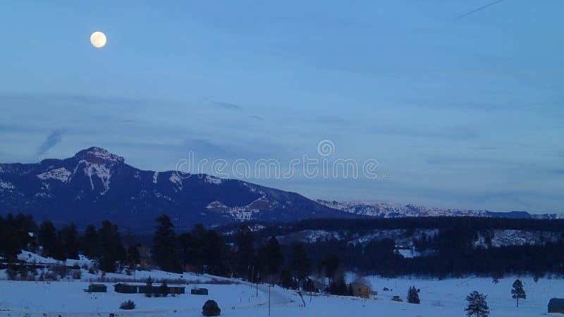 Fullmåne över bergen i vinter royaltyfri bild