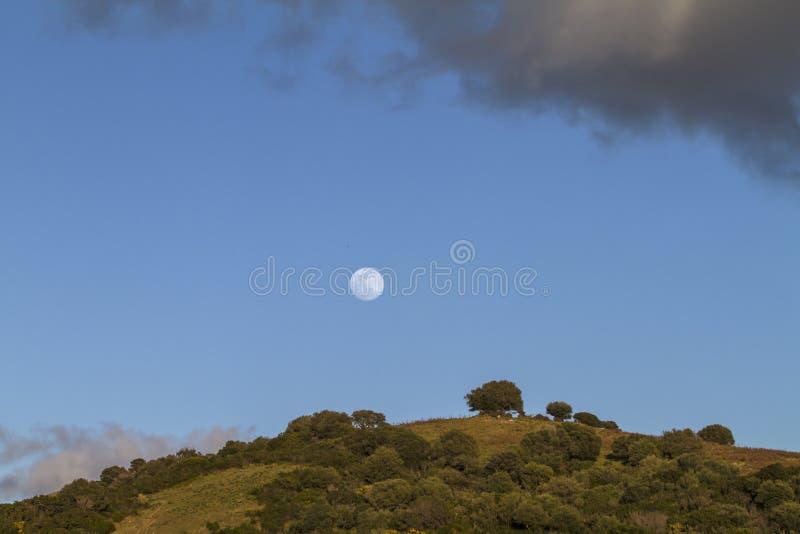 Fullmåne i blå himmel för skymningtid utom fara med ett moln som vilar på kullen under, och en annan svart som över hotar royaltyfria bilder