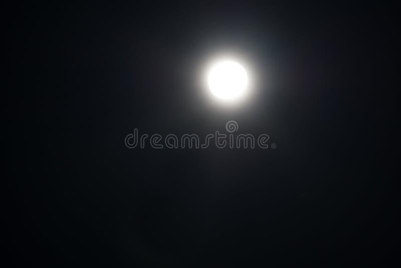 Fullmåne som ses med ett astronomiskt teleskop över blå himmel arkivfoto