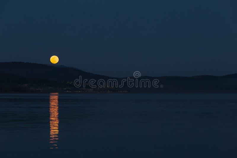 Fullmåne som stiger över några kullar på en sjö som reflekterar perfekt arkivbild