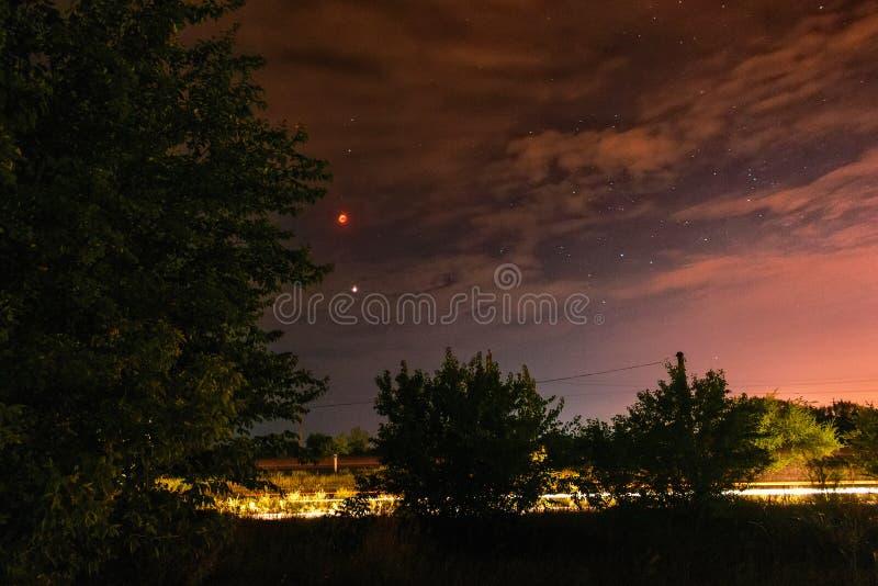 Fullmåneförmörkelse på den molniga mörka natthimlen fotografering för bildbyråer