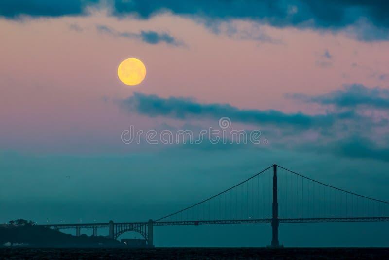 Fullmåneinställningen bak Golden gate bridge och dimman precis för soluppgång arkivbilder