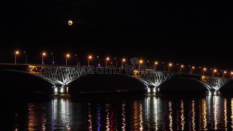 Fullmånelöneförhöjningar över bron Vägbro mellan städerna av Saratov och Engels, Ryssland Volgaet River Aftonljusen fotografering för bildbyråer