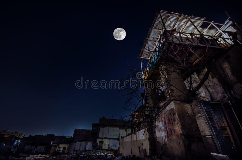 Fullmånen över fördärvar av gammal grungebyggnad i Baku på natten, hus med balkongen Sovetsky Azerbajdzjan arkivfoto