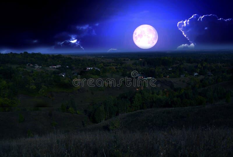 Fullmånen stiger över kullarna arkivbild