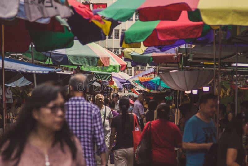 Fullsatt gatamarknad med färgglade paraplyer i Asien royaltyfria bilder