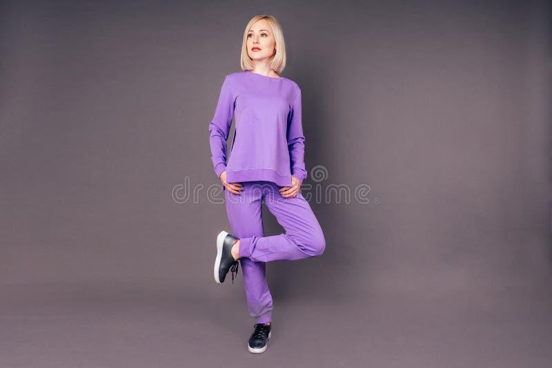 Fullständig porträtt av en vacker, blond, slimmad kvinna i en violett idrottsdräkt som ställer till med och sträcker sig i studio arkivbilder