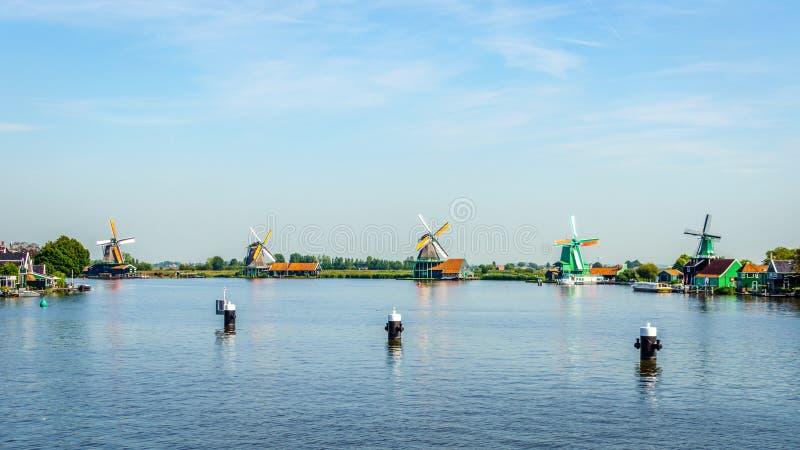 Fullständigt - fungerande historiska holländska väderkvarnar och hus längs den Zaan floden arkivfoton
