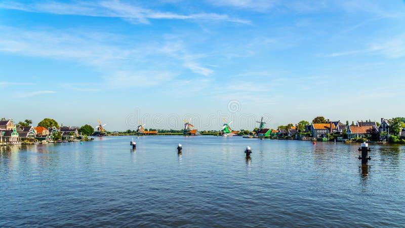 Fullständigt - fungerande historiska holländska väderkvarnar och hus längs den Zaan floden royaltyfri fotografi