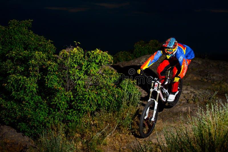 Fullständigt utrustad yrkesmässig sluttande cyklist som rider cykeln på natten Rocky Trail royaltyfria foton