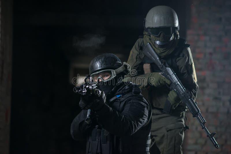 Fullständigt utrustade militära män med automatiska vapen arkivfoton