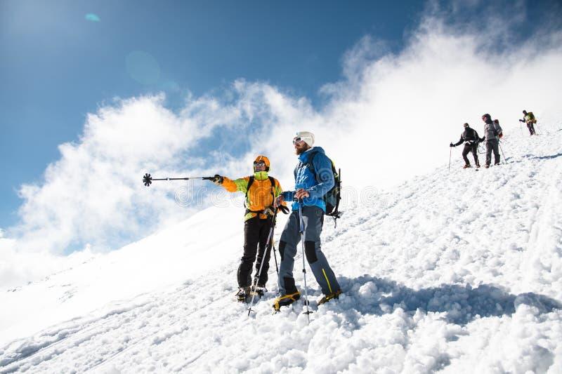 Fullständigt utrustade yrkesmässiga klättrare stiger ned ner den snöig lutningen i soligt väder arkivbild
