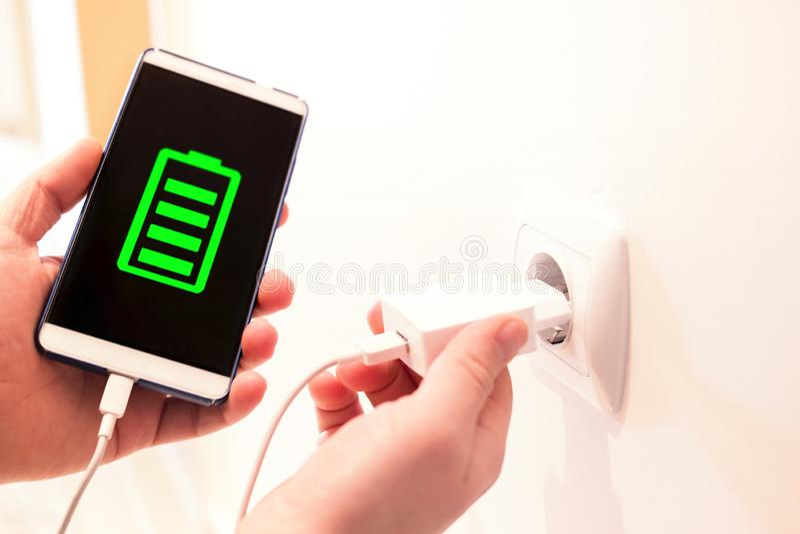 Fullt batteri som laddas av en uppladdare telefon som laddar från ett vägguttag fotografering för bildbyråer