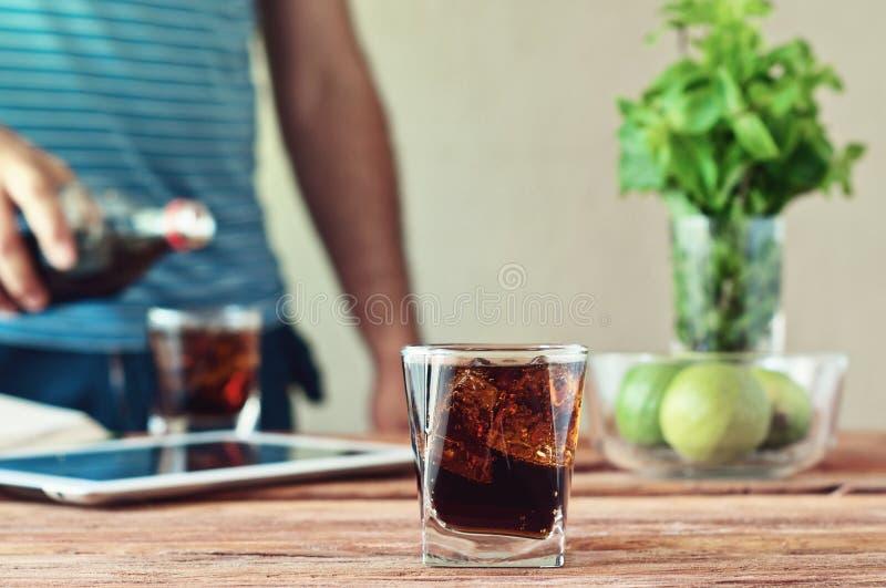 Fullt exponeringsglas av cola i förgrunden på trätabellcloseupen arkivfoto