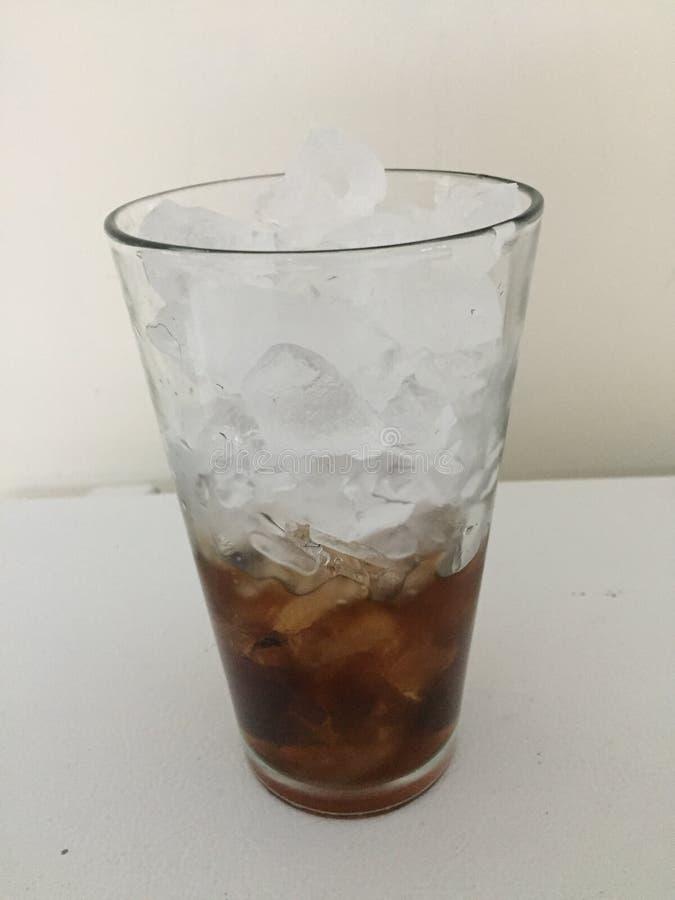 Fullt exponeringsglas av is med ett halvfullt exponeringsglas av cola royaltyfri fotografi