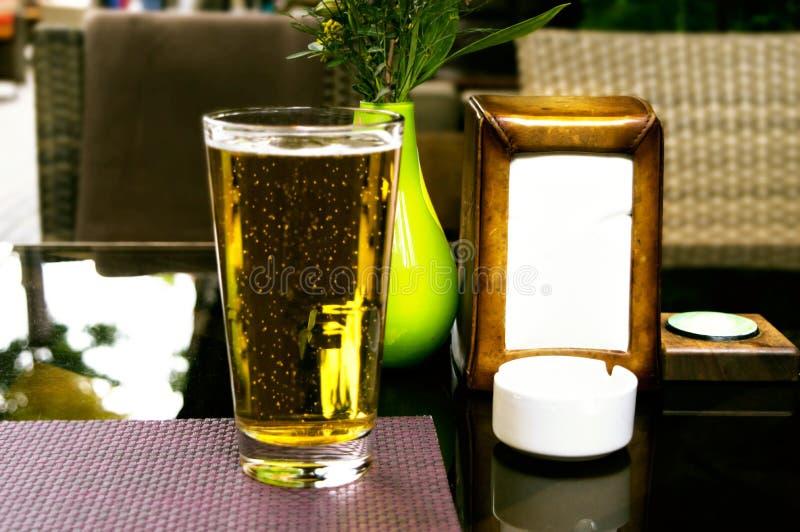 Fullt exponeringsglas av nytt öl på en tabell royaltyfri bild