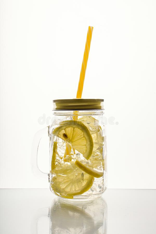 Fullt exponeringsglas av nytt kallt genomskinligt vatten med citronen och is arkivbild