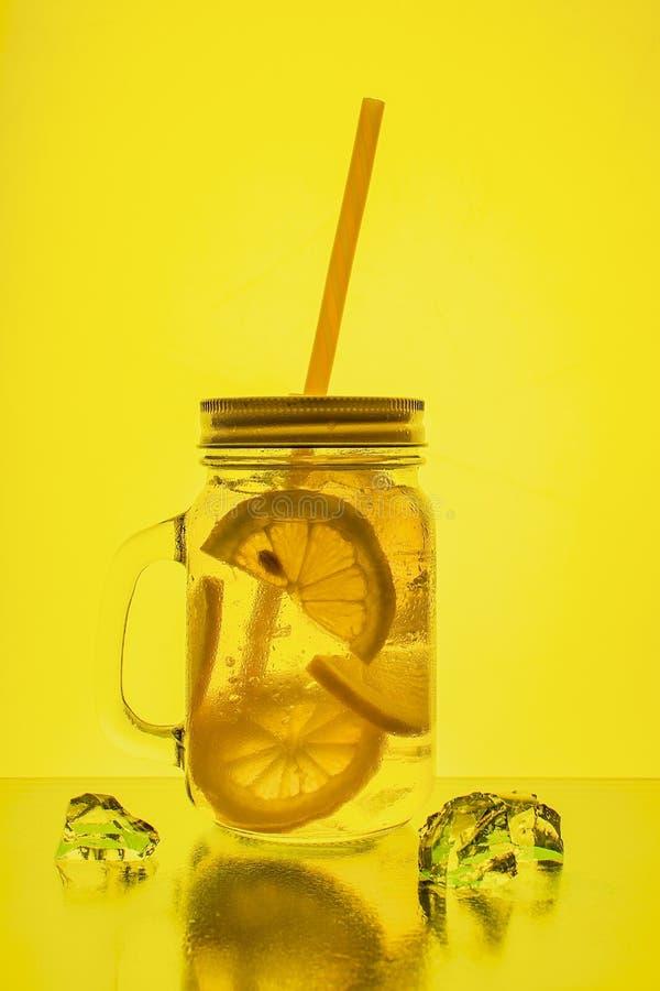 Fullt exponeringsglas av nytt kallt genomskinligt vatten med citronen och is royaltyfria bilder