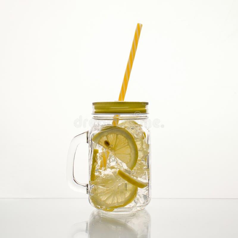 Fullt exponeringsglas av nytt kallt genomskinligt vatten med citronen och is royaltyfri fotografi