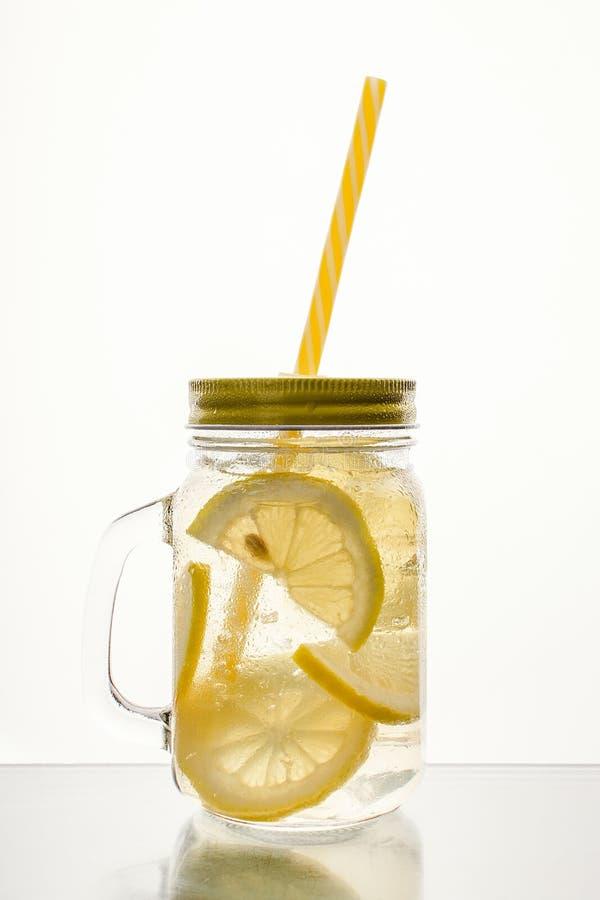 Fullt exponeringsglas av nytt kallt genomskinligt vatten med citronen och is fotografering för bildbyråer