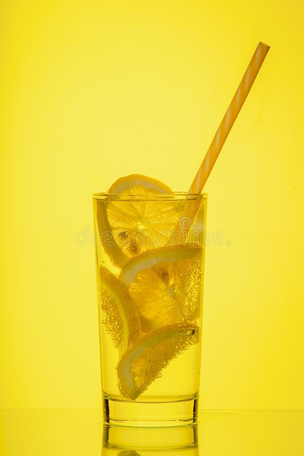 Fullt exponeringsglas av nytt kallt genomskinligt vatten med citronen p? gul bakgrund fotografering för bildbyråer