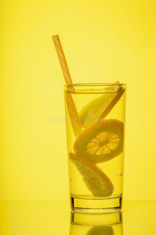 Fullt exponeringsglas av nytt kallt genomskinligt vatten med citronen p? gul bakgrund royaltyfri bild