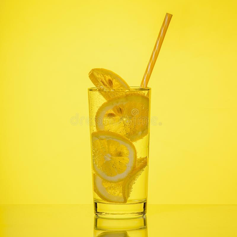 Fullt exponeringsglas av nytt kallt genomskinligt vatten med citronen p? gul bakgrund royaltyfria bilder