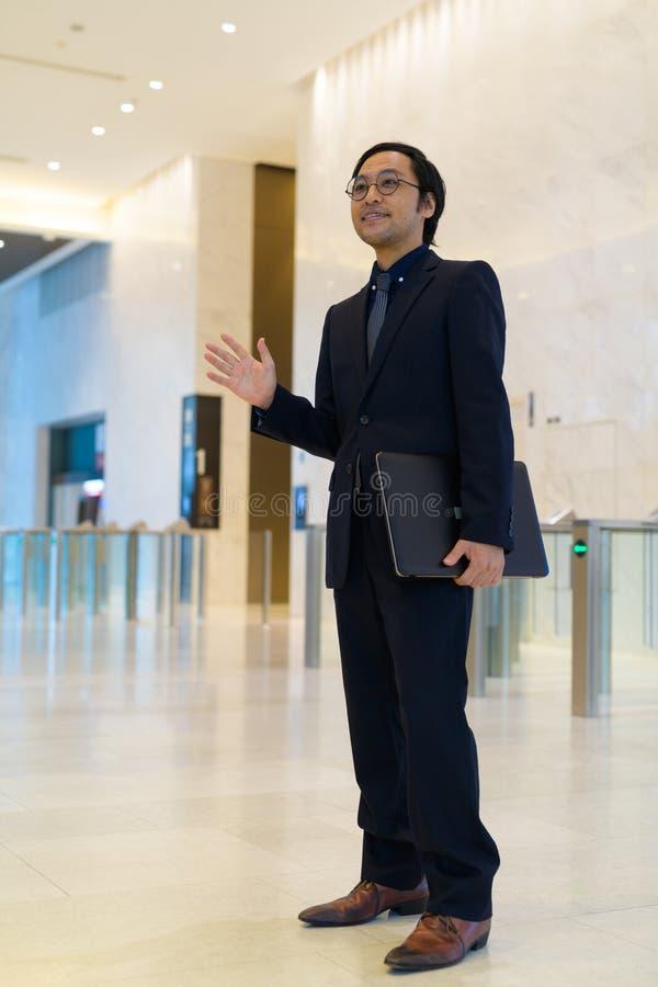 Fullt kroppskott av den lyckliga asiatiska affärsmaninnehavbärbara datorn och den vinkande handen royaltyfri bild