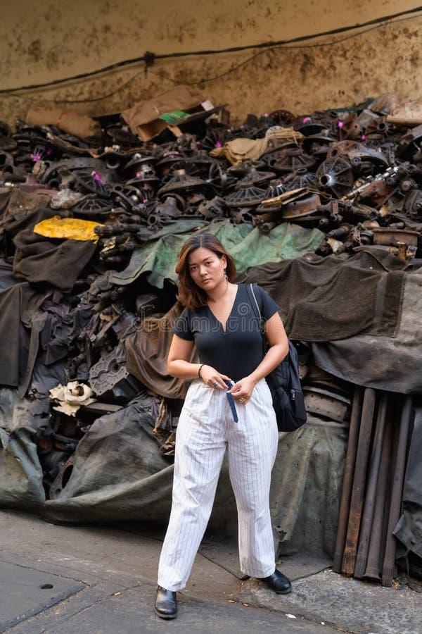 Fullt kroppskott av den unga härliga asiatiska turist- kvinnan i smutsig gränd arkivbild