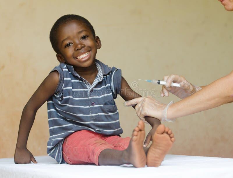 Fullt kroppskott av ett lyckligt afrikansvartbarn som får en visarinjektion som en medicinsk vaccinering royaltyfri fotografi