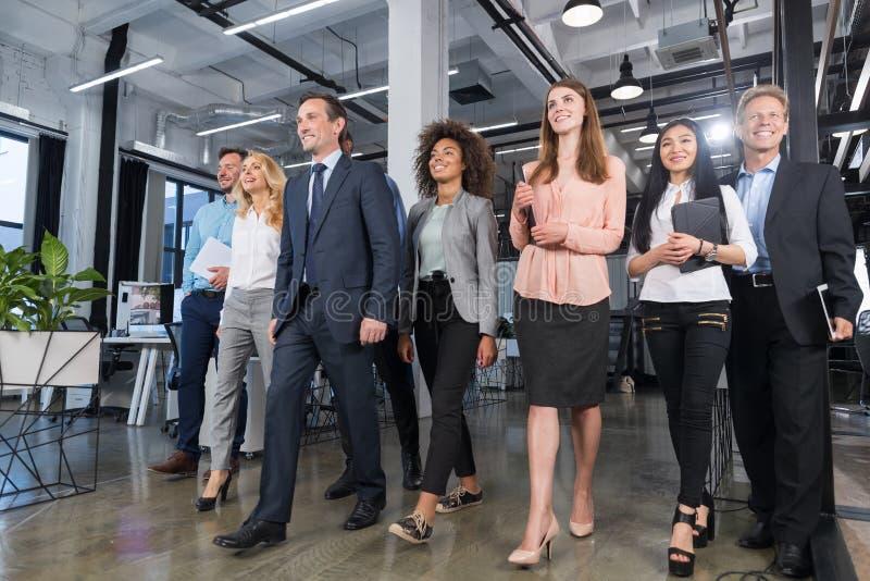 Fullt längdaffärsfolk Team Walking In Modern Office, säkra affärsmän och affärskvinnor i dräkter som är olika med