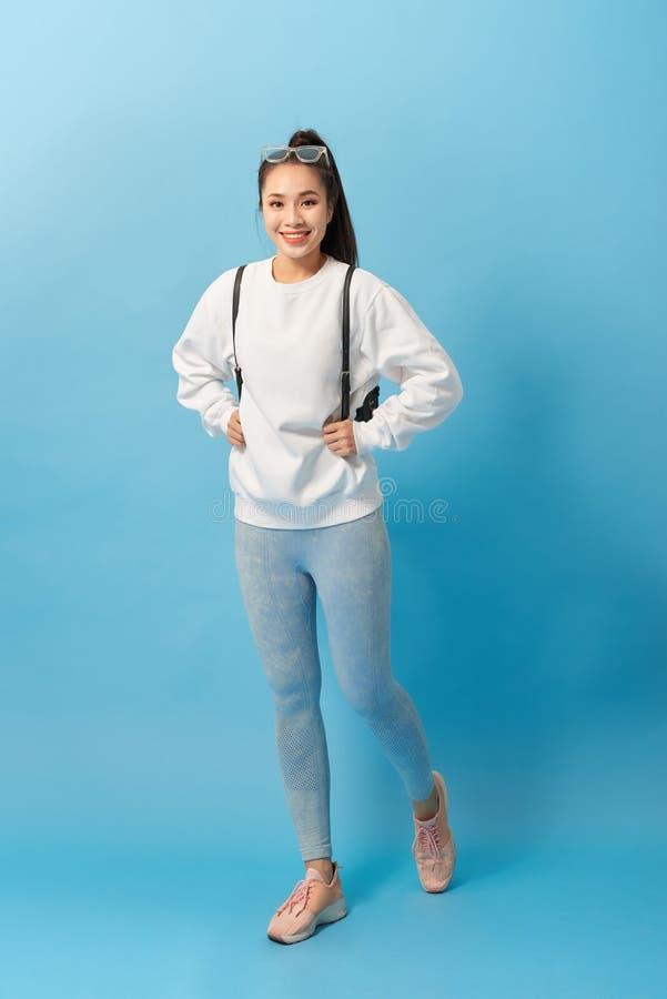 Fullt längdfoto av den asiatiska kvinnastudenten som går med ryggsäcken som isoleras över ljust - blå bakgrund arkivfoto