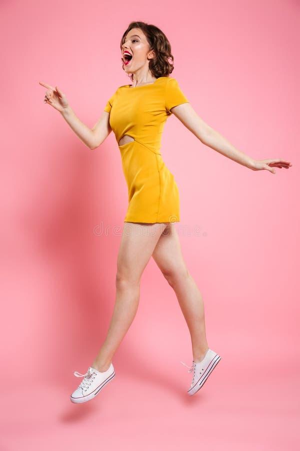 Fullt längdfoto av den nätta flickan med röd kantmakeup som pekar w arkivfoto
