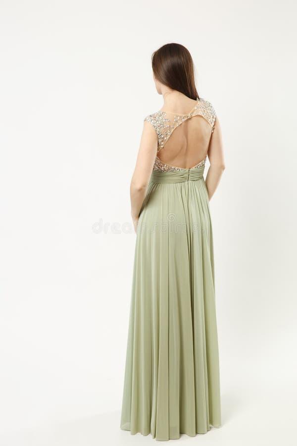 Fullt längdfoto av kvinnan för modemodell som bär elegant posera för kappa för aftonklänning som olivgrönt isoleras på den vita v arkivbild