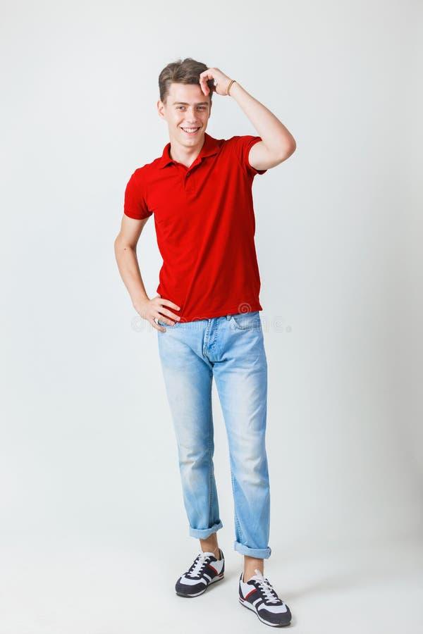 Fullt längdfoto av vänskapsmatchen som ser den gladlynta europeiska grabben som bär den röda skjortan och jeans som ler anseende  arkivfoton