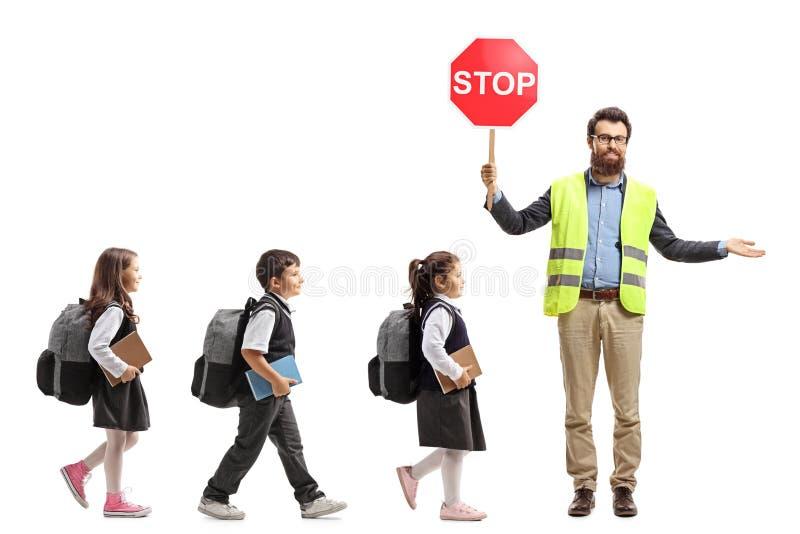 Fullt längdskott av skolbarn som går i en linje och en lärare med ett säkerhetsväst- och stopptecken som visar vägen royaltyfri bild