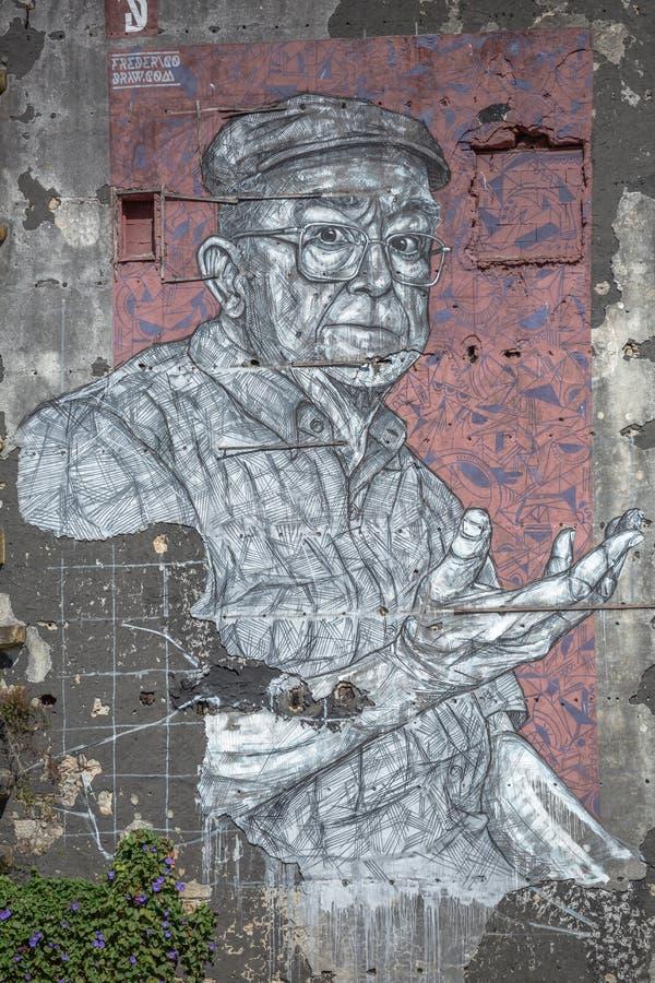 Fullt - sikt av konstverk som målar på den yttre väggen av byggnad, med illustrationen av äldre man som mycket är uttrycksfull arkivfoto