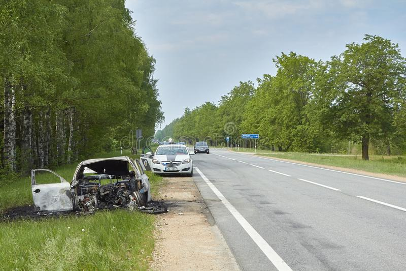 Fully burned car on roadside after collision with heavy truck  in May 23, 2019, in Latvia, next to Pinki stock image
