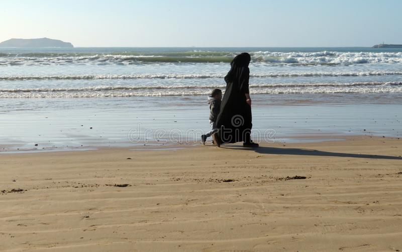 A fully covered Muslim woman in black niqab and abaya walking with her little son on the beach stock photography
