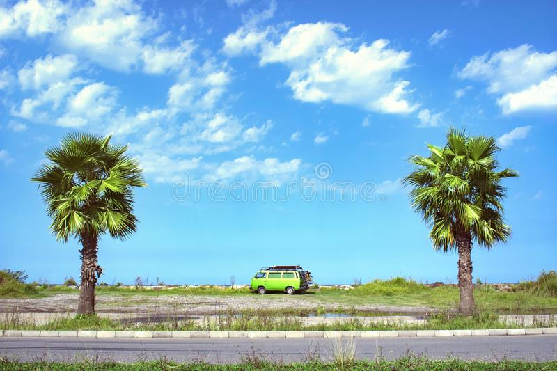 Fully equipped old timer camper van parked on the beautiful long beach between two palm trees on a bright sunny summer day stock image