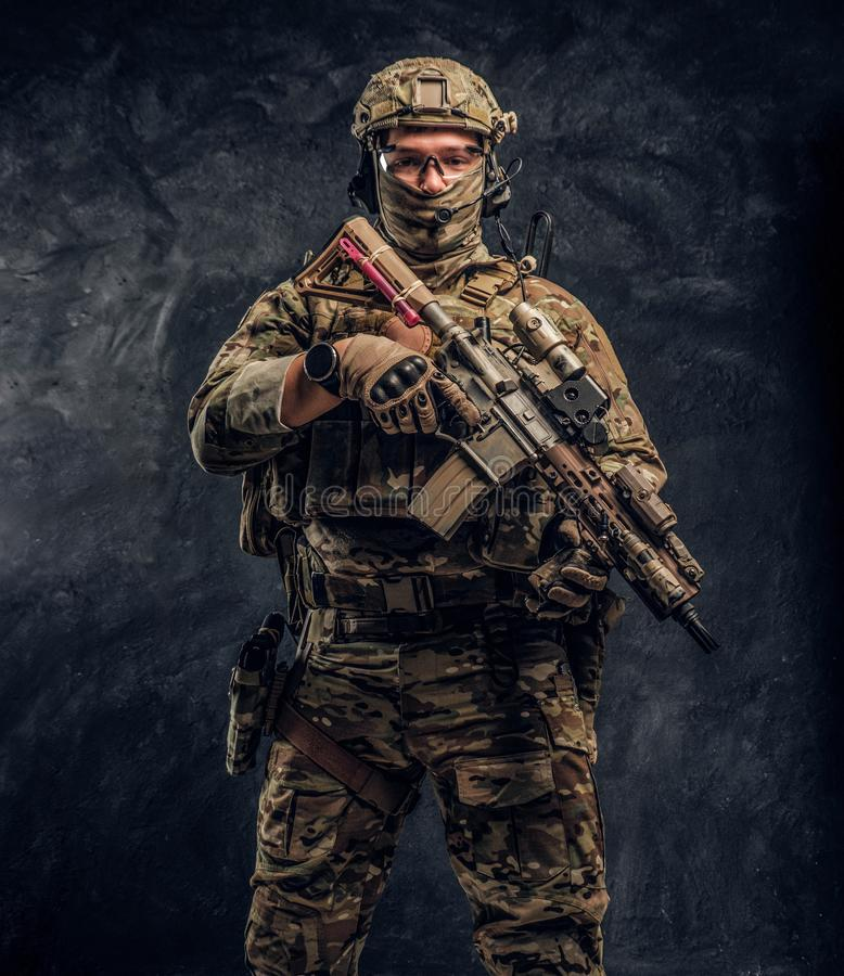 Fully equipped soldier in camouflage uniform holding an assault rifle. Studio photo against a dark wall royalty free stock photos