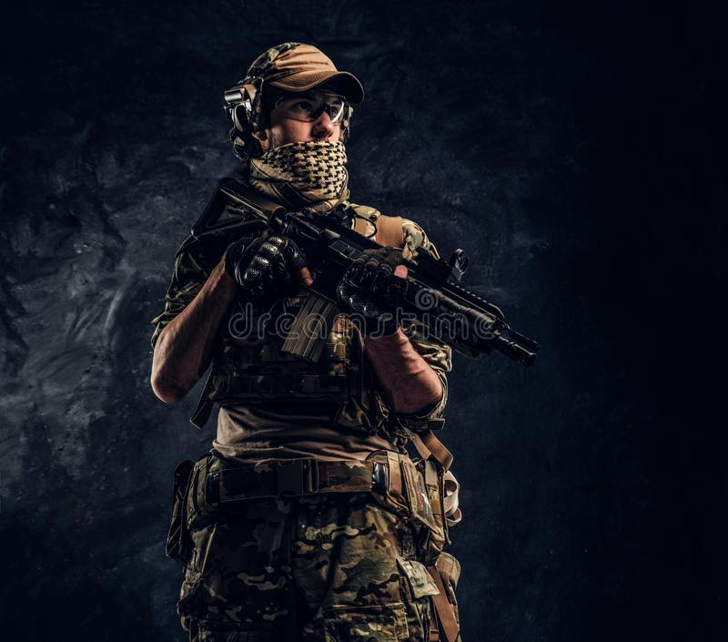 Fully equipped soldier in camouflage uniform holding an assault rifle. Studio photo against a dark wall stock image